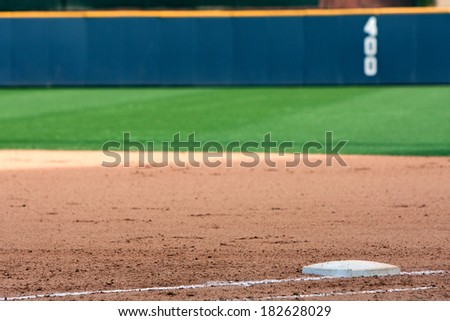 Empty baseball field highlights first base and outfield wall. - stock photo