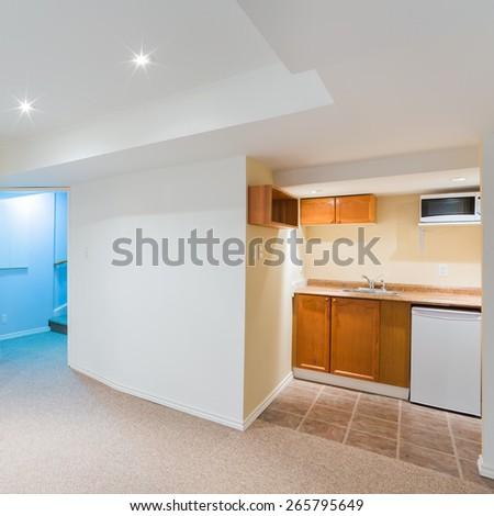 Empty basement living room with kitchen design - stock photo