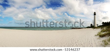 Empty beach and light house in tropical environment - stock photo