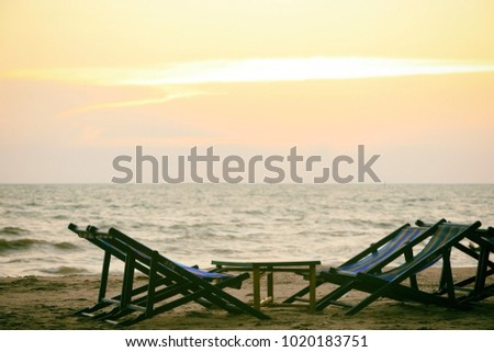 Empty beach chair on the beautiful tropical beach and sea at sunset time.