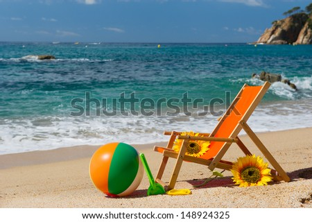 Empty beach chair with flowers and toys at the sea