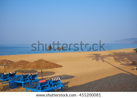 empty beach chairs on a tropical beach - stock photo