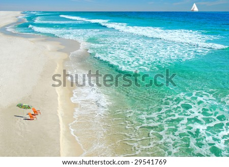 Empty beach chairs on deserted beach with sailboat in distance - stock photo