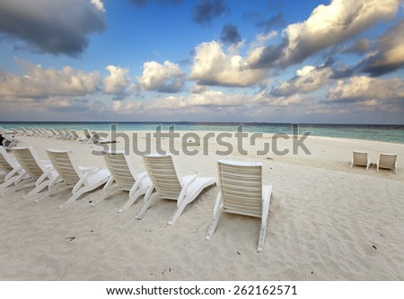 Empty beach chairs on sand by the sea at sunrise - stock photo