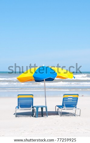 Empty beach chairs waiting for vacationers - stock photo