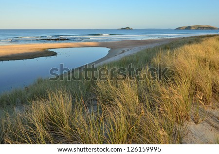 Empty beach during sunset in New Zealand - stock photo