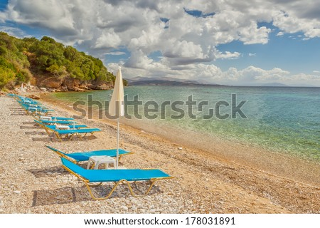 Empty beach Lounge chairs under bright sunlight at the shore of Ionian sea near Ipsos beach, Corfu, Greece - stock photo