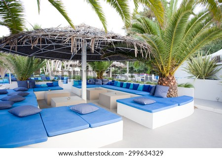 Empty beach lounge with white furniture and blue pillows under straw parasols and big palms - stock photo