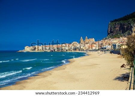 empty beach of Cefalu leading to its old town in a sunny spring day, Sicily - stock photo