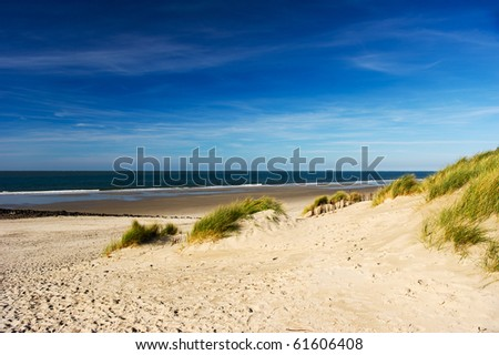 Empty beach with dunes waves and the sea - stock photo