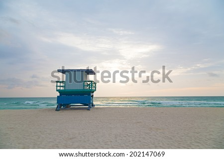 Empty beach with lifeguard cabin at sunrise. A lonely cabin on the empty beach. - stock photo