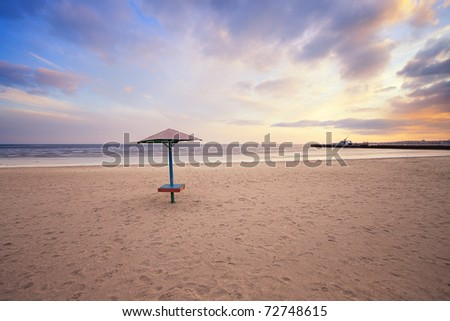 empty beach with lonely umbrella at sunset - stock photo