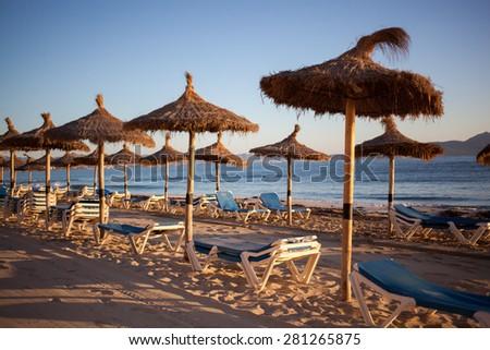Empty beach with straw umbrellas on sunrise in Spain, Mallorca - stock photo
