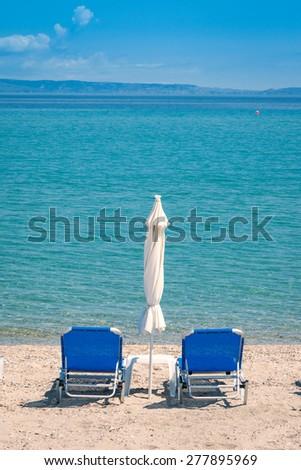 Empty beach with sunbeds - stock photo