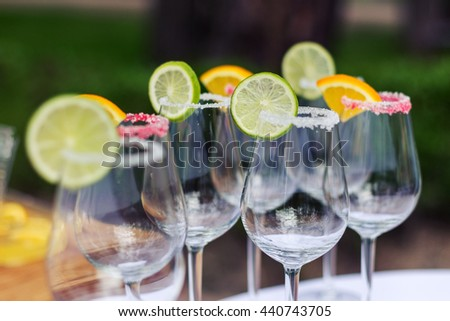 Empty beautiful glasses with slices of lime and lemon, decorated with sugar. Prepared for the lemonade. - stock photo