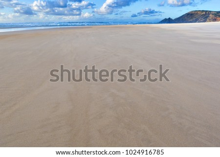 Empty beautiful sandy beach and cloudy blue sky background. Summer season holiday, vacation concept.