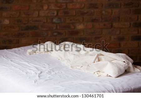 Empty bed and white sheet and cover with a brown brick wall in the background - stock photo