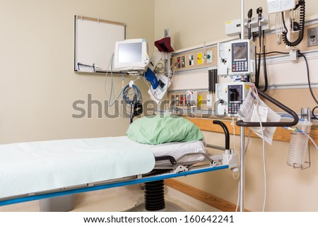 Empty bed with medical tools in hospital - stock photo