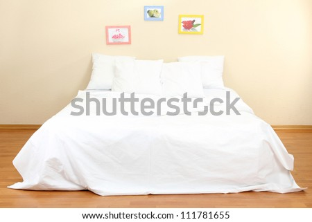 Empty bed with pillows and sheets in bedroom - stock photo