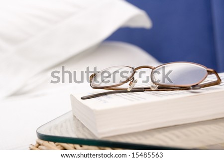 Empty bedroom with focus on eyeglasses and book