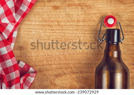 Empty Beer Bottle with Swing Flip Top Stopper on Wooden Table with red and White Checkered Tablecloth and Copy Space - stock photo