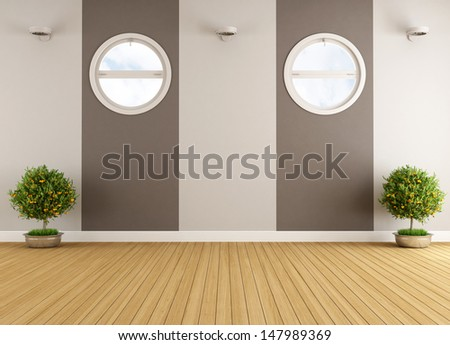 Empty beige and brown interior with two round windows - stock photo