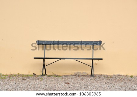 Empty bench against empty wall.
