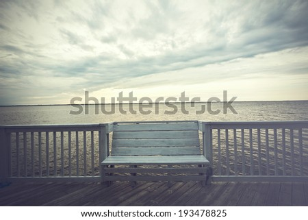 Empty bench along the boardwalk overlooking the Currituck sound in Duck in the Outer Banks of North Carolina - stock photo