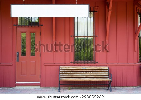 Empty bench by blank sign against red wooden walls - stock photo