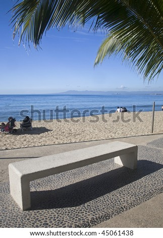 Empty bench by the beach - stock photo