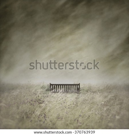 Empty bench in a wild, lonely, windswept landscape captured using long exposure, bokeh and other effects with some areas blurred to create a surreal and dreamlike effect.