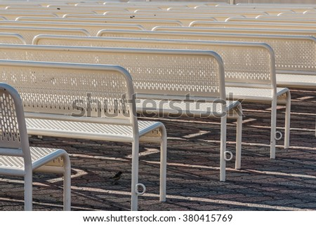 Empty benches in rows from behind facing right. - stock photo