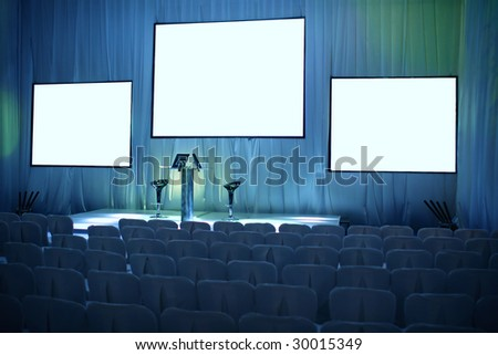 Empty big conference hall with podium and three screens - stock photo