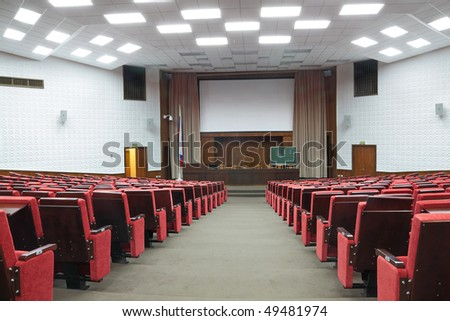 Empty big white conference room with red armchairs - stock photo