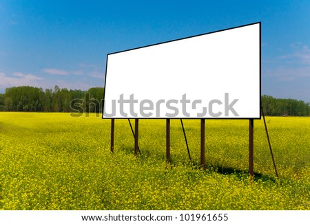 Empty billboard for your advertise on yellow rapeseed flower field - stock photo