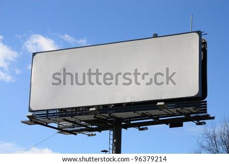 Empty billboard on blue sky background. - stock photo