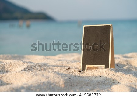 Empty black board on white sand beach with warm sunlight - stock photo
