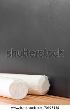 Empty black chalkboard with piece of chalk - stock photo
