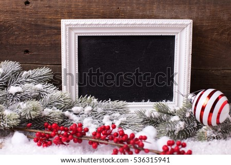Empty blackboard, decorative berries , ball and branches fur tree on aged  wooden background.  Decorative christmas composition. Selective focus. Place for text.