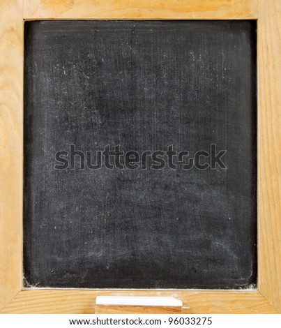 Empty blackboard with a wooden frame and chalk - stock photo