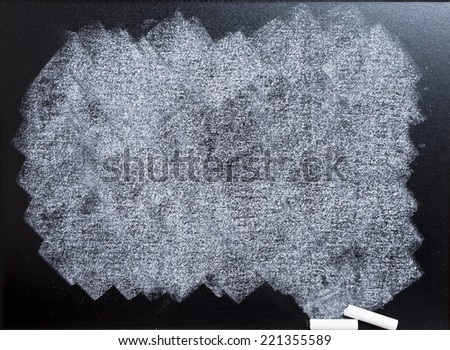 empty blackboard wooden framed soiled with dust of chalk rubbed and a broken chalk - suitable for copy space - stock photo