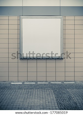 Empty blank square white advertising billboard on tiled wall. Information. Promotion of your product. Real. Sepia tone. - stock photo