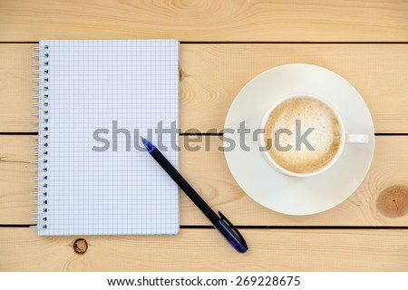 Empty blank with pen and cup of coffee on wooden table   - stock photo