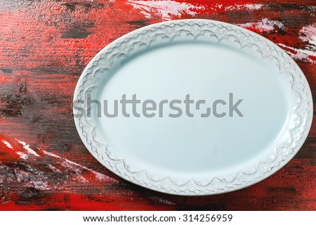 Empty blue ceramic oval plate with ornament over red-black wooden background. Top view. - stock photo