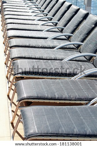 Empty blue deck chairs on a cruise ship - stock photo