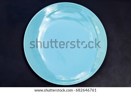 empty blue dish with black background textures