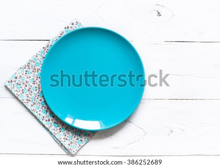 Empty blue plate and napkin at wooden table. View from above, copy space. - stock photo