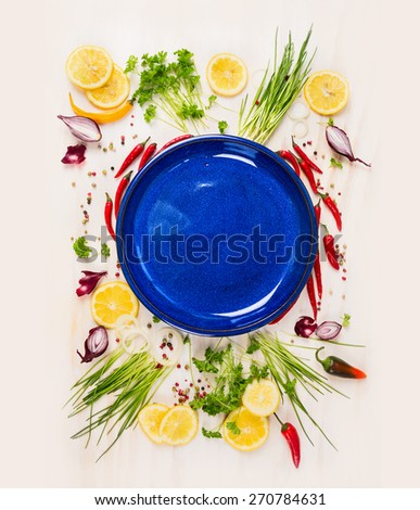 Empty blue plate with fresh seasoning and spices on withe rustic wooden background, top view, place for text - stock photo