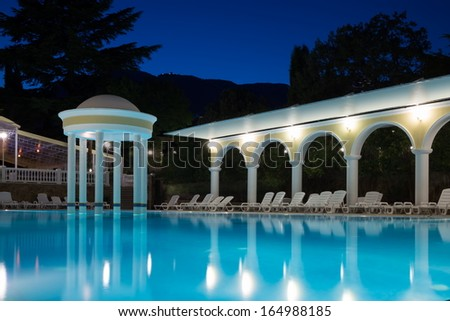 Empty blue swimming pool with loungers around in the evening