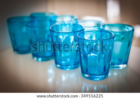 Empty blue water glasses set in restaurant